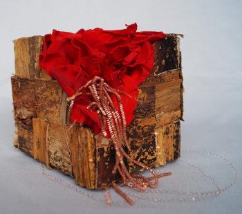 Composition en cube de carton dur, fibre de bananier, pétales de roses rouges et fil doré